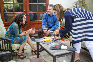 Three mature adult friends at garden party on patio