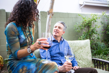 Mature couple chatting on patio at garden party