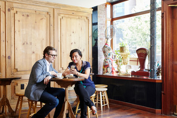 Man and woman sitting in cafe drinking coffee, looking at smartphone
