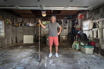Portrait of senior man standing in garage holding broom