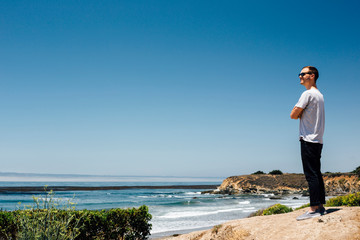 Man looking out over coast and sea, Cambria, California, USA