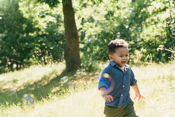 Male toddler running among floating bubbles in Pelham Bay Park, Bronx, New York, USA