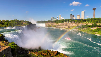 Niagara Falls and rainbow from the American side with the skyline of the city of Niagara Falls