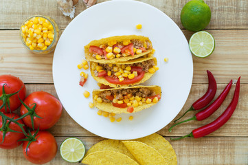Colorful mexican tacos cooked with crispy taco shells, yellow corn, red tomato and chicken mince