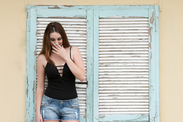 Tall woman standing against old wooden window, wearing shorts and decollete black shirt