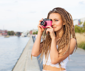 Portrait of Trendy Girl with Dreads and Vintage Camera Standing by the River. Modern Youth Lifestyle Concept. Take the picture.