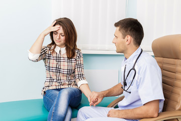 at a reception at the doctor Female patient holding his head. Visit a doctor in the hospital sick woman. Migraine