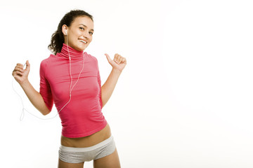 Image of smiling woman listening music and raising hands