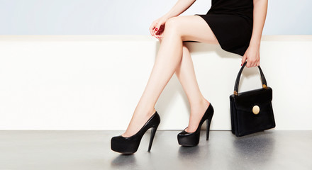 Beautiful legs woman with leather black shoes and handbag purse.
