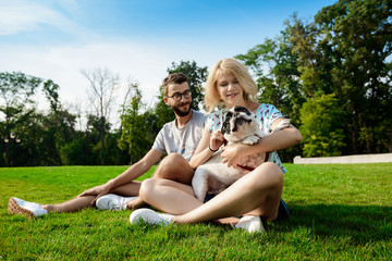 Couple smiling, sitting on grass with French bulldog in park.