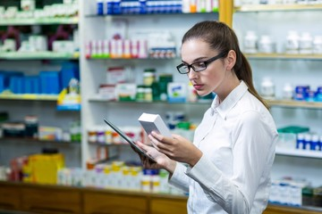 Pharmacist using digital tablet while checking medicine