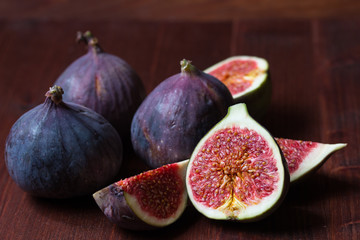 Whole and sliced figs on the dark wooden background. Selective focus.