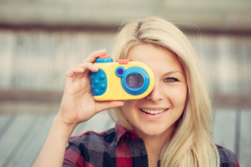 Beautiful blonde with long hair looking at the camera, smiling and holding in hands toy camera. Close up.