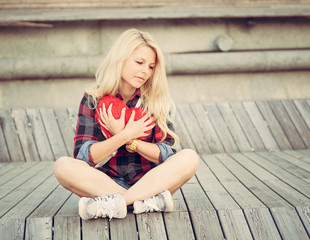Sad lonely girl sitting on wood planks and hugging a big red heart