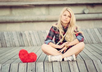 Sad lonely girl sitting on wood planks near to a big red heart