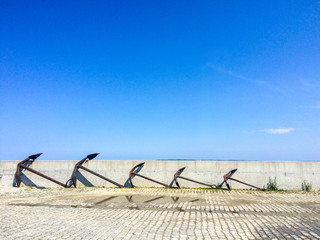 Five old decorative anchors standing in row at sea port