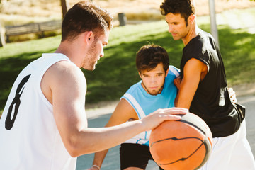 Portrait of group of friends playing basketball on court.