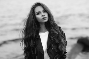 Young pretty stylish girl in black leather jacket posing, walking or standing at beach against water in bokeh. Fashionable woman with long curly hair looking at you.