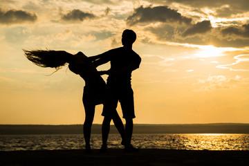 Couple dancing at sunset salsa / brazilian zouk. Lovers, dance partners spinning, latin festival dance concept.
