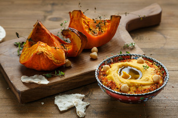 Pumpkin hummus and roasted butternut squash on background