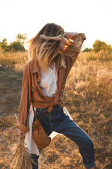 Beautiful blonde in blue jeans, a white shirt and brown jacket posing in a field and holding a bouquet with spikelets. Boho style