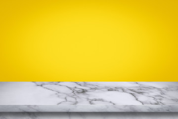 Empty top of marble table on yellow gradient wall background.