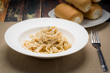 Fettuccine Alfredo classic Italian Pasta on a dark wood table..