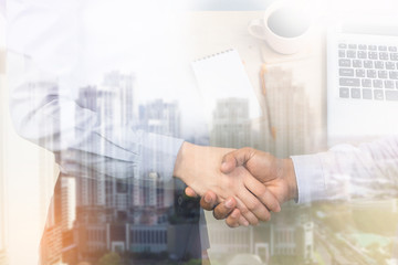 Businessman handshake on the city and office desk background