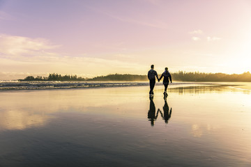 Sunset at the beach. Tofino Long Beach during the summer. Couple going for a walk as the sun sets.
