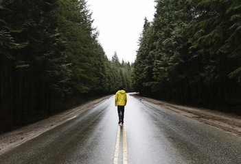 Fotomurales - Person walking a road in the forest. Pacific North West, Vancouver British Columbia Canada. Straight road with evergreen trees on both sides.