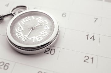 Old pocket watch on calendar page. vintage, black&white