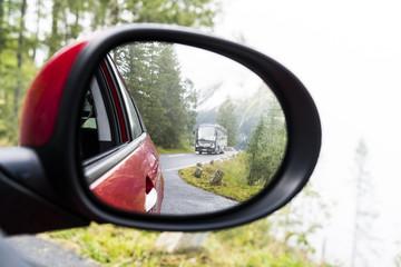 PKW-Rückspiegel mit Reisebus und Alpenpanorama
