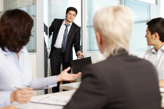 Office worker coming late to meeting