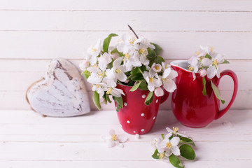 Apple tree flowers and heart  on white wooden background.