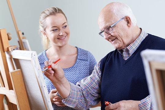 Senior Man Attending Painting Class With Teacher