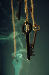 Keys hanging on a string. Smoke background. Selective focus