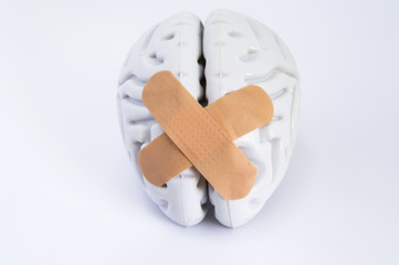 Hemispheres of human brain, stuck together using beige adhesive tape, lying on white background. The idea for visualizing treatment of neurological diseases such as the broken brain syndrome and other