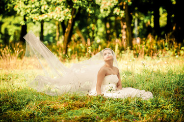 beautiful young bride sitting on a green meadow in the forest