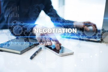 """Businessman is working in office, pressing button on virtual screen and selecting """"Negotiation"""". Business concept."""