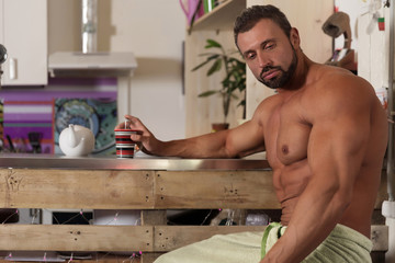 Muscle shirtless bachelor man have a breakfast in kitchen