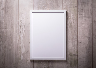 Blank white picture frame on the wood wall