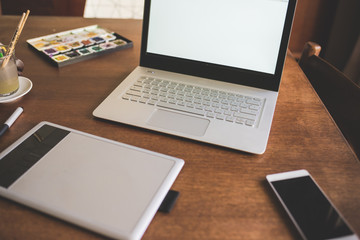 View of working desk with drawing table, notebook and smart phone on wooden table - working, creativity, business concept