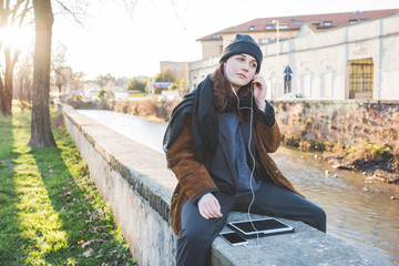 Young beautiful caucasian millennial woman sitting on a small wall listening music with earphones smart phone and tablet, overlooking serene - music, technology, positive concept