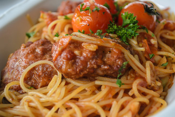 Spaghetti with meatballs in tomato marinara sauce and indegredient on plate