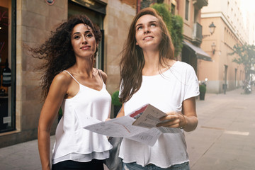 Two attractive hipster girls with long hairs are walking in the urban zone during the vacation. Friends wearing casual clothes are using map to find interesting places while travelling.