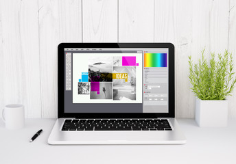 laptop on table graphic design software