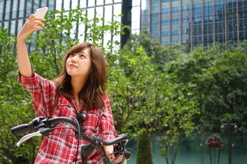 Young Asian woman taking Selfie (Self Portrait) riding on a bike in a city