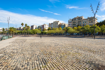 Pedestrian zone in front of the Barceloneta district Barcelona. The Plaza Muelle del Rellotge is part of  Port Vell Barcelona. Thousands of people stroll, roller skate or cycle along this quay