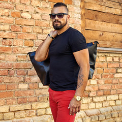 Fashion portrait of handsome man in sunglasses and black modern