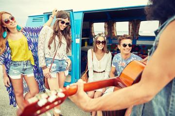 happy hippie friends playing music over minivan
